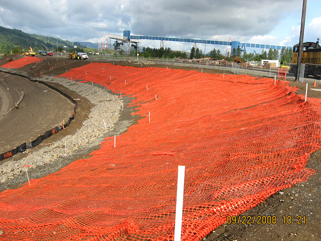 Wheeler Bay: Contractor placing orange demarcation fabric on newly graded slope prior to placing new top soil on top for plantings.