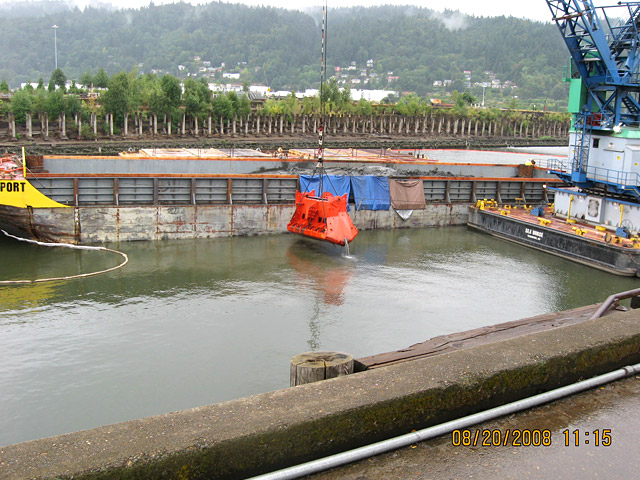 Dredging: Dredge bucket being raised to be emptied into the barge behind it.