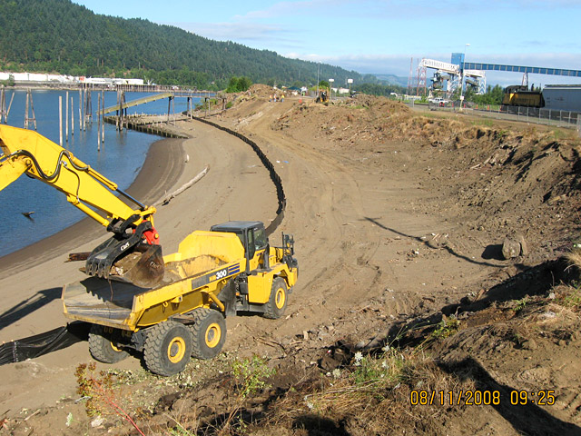 Wheeler Bay: Contractor removing debris from slope surface. Black silt fence delineates work area and helps avoid erosion during construction.